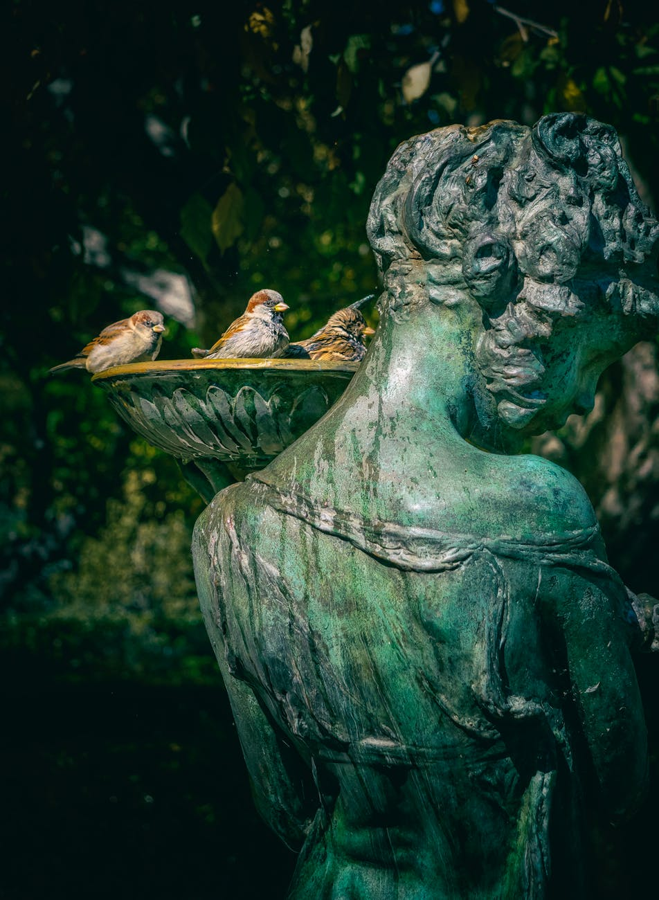 woman statue with bird bath